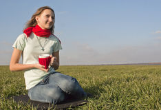 Teen girl sitting outdoors. With a cup Stock Photos