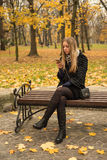 Teen girl sitting on a park bench in the fall with a smartphone Stock Photography