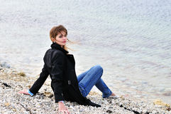Teen girl sitting on the pebble Stock Images
