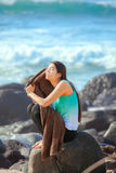 Teen girl sitting on rocky beach shore drying off Royalty Free Stock Images