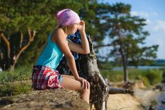 Teen girl sitting on sand cliff looking to sea. Travel and tourism concept Stock Photos