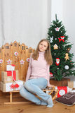 Teen girl sitting on sledge with presents and Christmas tree Stock Photo