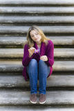 Teen Girl Sitting On Stairs. Pretty Blond Teen Girl Sitting on Stairs Holding a Daisy Royalty Free Stock Photography