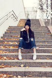 Teen girl sitting on stairs against grunge wall Stock Photo