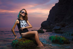 Teen girl sitting on stone fashion shoot at sunset Stock Image