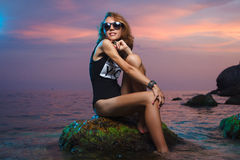 Teen girl sitting on stone fashion shoot at sunset Stock Photos