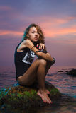 Teen girl sitting on stone fashion shoot at sunset Stock Photo
