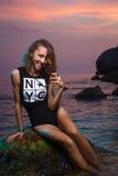 Teen girl sitting on stone fashion shoot at sunset Royalty Free Stock Image