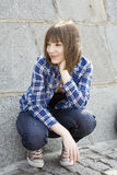 Teen girl sitting at stone wall Royalty Free Stock Photo
