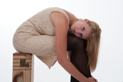 Teen girl sitting on a suitcase Stock Images