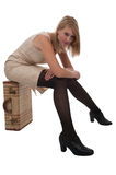 Teen girl sitting on a suitcase Royalty Free Stock Images