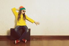 Teen girl sitting on a suitcase in anticipation of holiday travel. Royalty Free Stock Photography