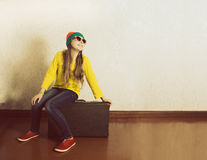 Teen girl sitting on a suitcase in anticipation of holiday travel. Stock Image