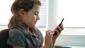 Teen girl sitting by the window with the smartphone playing online games Stock Photos