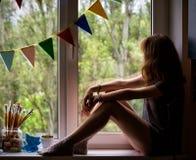 Teen girl sitting on a windowsill 5 stock photos