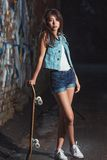 Teen girl with skate board Royalty Free Stock Image