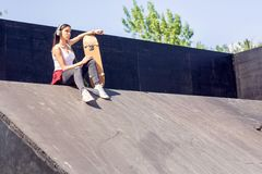 Teen girl with skateboard listening music in skate park royalty free stock images