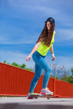 Teen girl skater riding skateboard on street. Summer sport and active lifestyle. Cool teenage girl skater riding skateboard on the street. Outdoor royalty free stock image