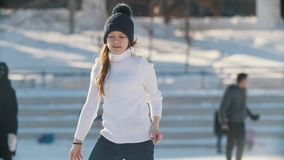 Teen girl skillfully skating on outdoor public ice rink, slow-motion. Youth pastime and rest stock video footage