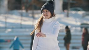 Teen girl skillfully skating on outdoor public ice rink, slow-motion. Youth pastime and rest stock footage