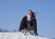 Teen girl sledding. From a hill Royalty Free Stock Photo