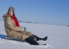 Teen girl sledding from a hill. At snowy sunny day Royalty Free Stock Photos