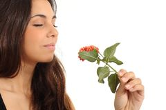 Teen girl smelling a flower. With her eyes closed in a white background Stock Photo