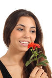 Teen girl smelling a flower. Smiling in a white background Stock Images