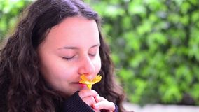 Teen girl smelling flower in slow motion Royalty Free Stock Image