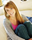 Teen girl smiling. With arms around knees Royalty Free Stock Image