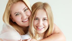 Teen girl smiling. Close up portrait of a mother and teen daughter being close and hugging at home being happy and joyful Royalty Free Stock Image