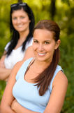 Teen girl smiling with mother in background Royalty Free Stock Images