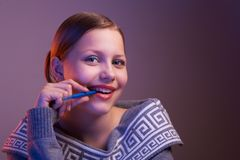 Teen girl smiling with pen in her hand, portrait Stock Photos