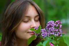 Teen girl sniffing lilacs. Portrait of a beautiful teenage girl sniffing lilacs with closed eyes Royalty Free Stock Image