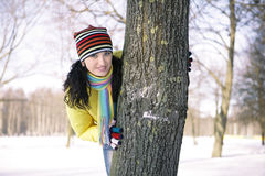 Teen girl with snowball, surprised. Girl in a yellow jacket in the park in winter snowball, hiding behind a tree Royalty Free Stock Image