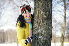Teen girl with snowball, surprised. Girl in a yellow jacket in the park in winter snowball, hiding behind a tree Royalty Free Stock Photography
