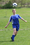 Teen Girl Soccer Player In Action. With ball in Air During Soccer Game Stock Photo