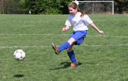 Teen Girl Soccer Player In Action. Teen Girl Soccer Player Kicking ball in the air Stock Photography