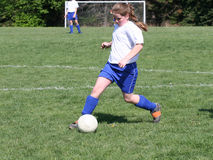 Teen Girl Soccer Player In Action. Teen Girl Soccer Player Kicking ball down the field during game Stock Images
