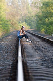 Teen girl sorrow on rail. Teen girl sitting and sorrow on rail at sunset with trees behind her stock photography