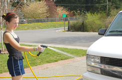 Teen girl sprays van with hose Stock Images