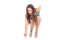 Teen girl squatting and pointing at the floor Stock Images