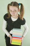 Teen girl with a stack of books. Teen girl with glasses holding a stack of books Royalty Free Stock Image
