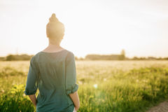Teen girl stand on rural road shot from back Stock Photo