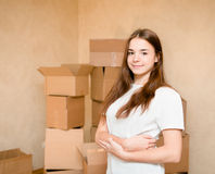 Teen girl standing on a background of cardboard boxes royalty free stock photography