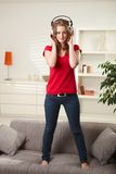 Teen girl standing on couch with headphones Royalty Free Stock Photo