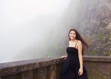 Teen girl standing on foggy hillside in black dress,  smiling Stock Photos