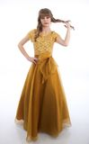 Teen Girl Standing in Formal Prom Gown. Teen girl stands against a white, isolated background while wearing a beautiful gold colored formal prom gown twirling Royalty Free Stock Images