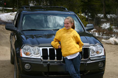 Teen girl standing in front of an SUV Royalty Free Stock Images