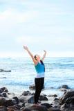 Teen girl standing on rocky beach arms raised, praising God. Beautiful biracial teen girl wearing exercise clothes standing on rocky beach arms raised, praising Stock Photography